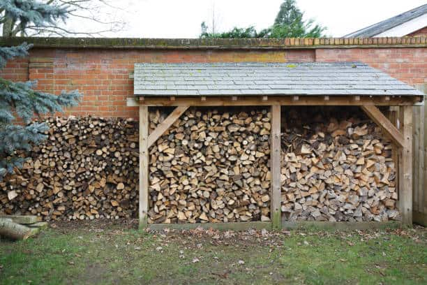 Log store filled with cut logs for firewood in a garden