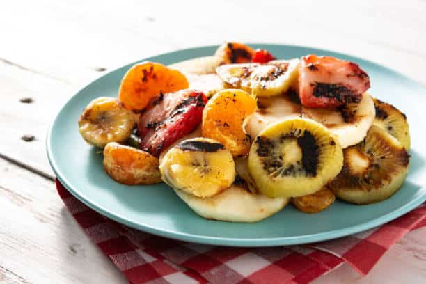 Grilled fruit on blue plate and white wooden table