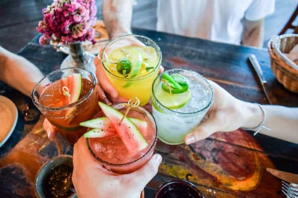 Friends toasting, saying cheers holding tropical blended fruit margaritas.  Watermelon and passionfruit drinks.
