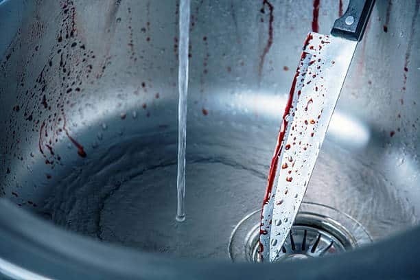 Cleaning bloody knife in kitchen sink